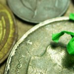 Green paper frog sitting on coins